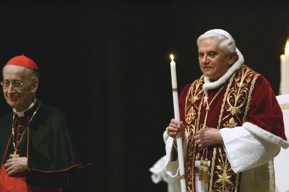 Pope Benedict XVI holds a candle flanked
