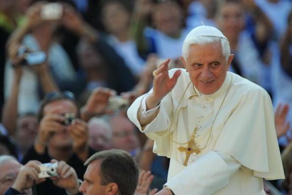 Pope Benedict XVI waves to faithful duri