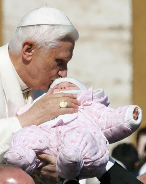 Pope Benedict XVI kisses a baby during h